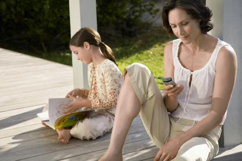 Mother and daughter enjoy time together outside on a porch.