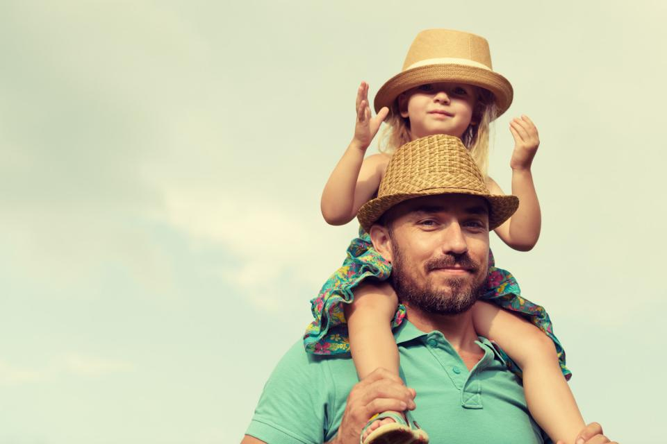 Father carries daughter on shoulders while outside on a sunny day