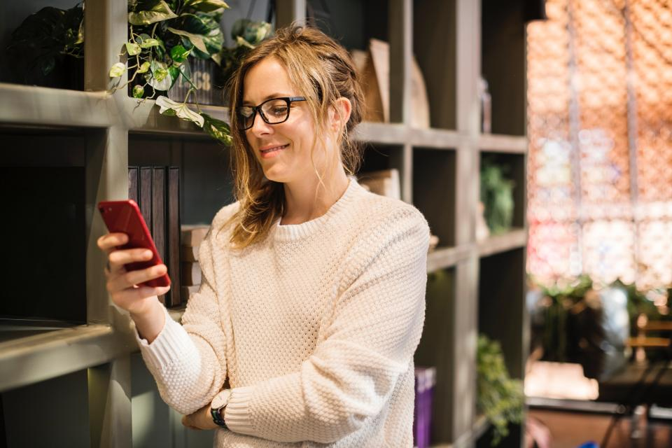 A woman smiles as she looks at her phone.