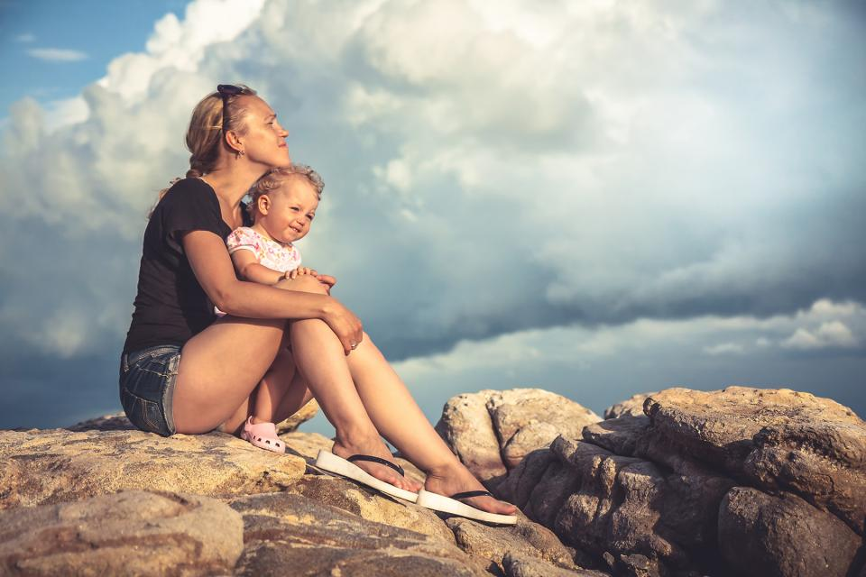 Mom holds young daughter in her lap as they sit on top of a rock.